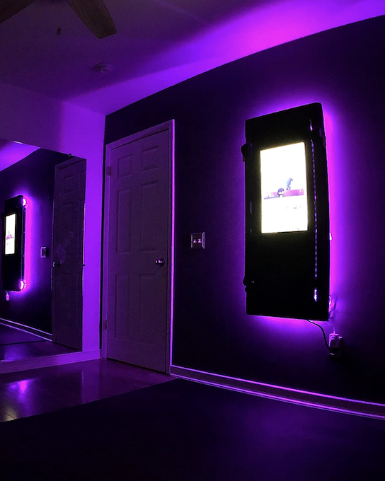 a tonal sits in a room with a purple light around it