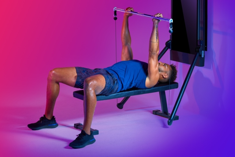 A man lies back on a bench and works on his bench press with Tonal — discover how to improve your bench press with data
