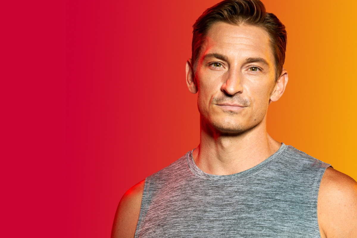 image of a man in a grey workout vest on a colourful background