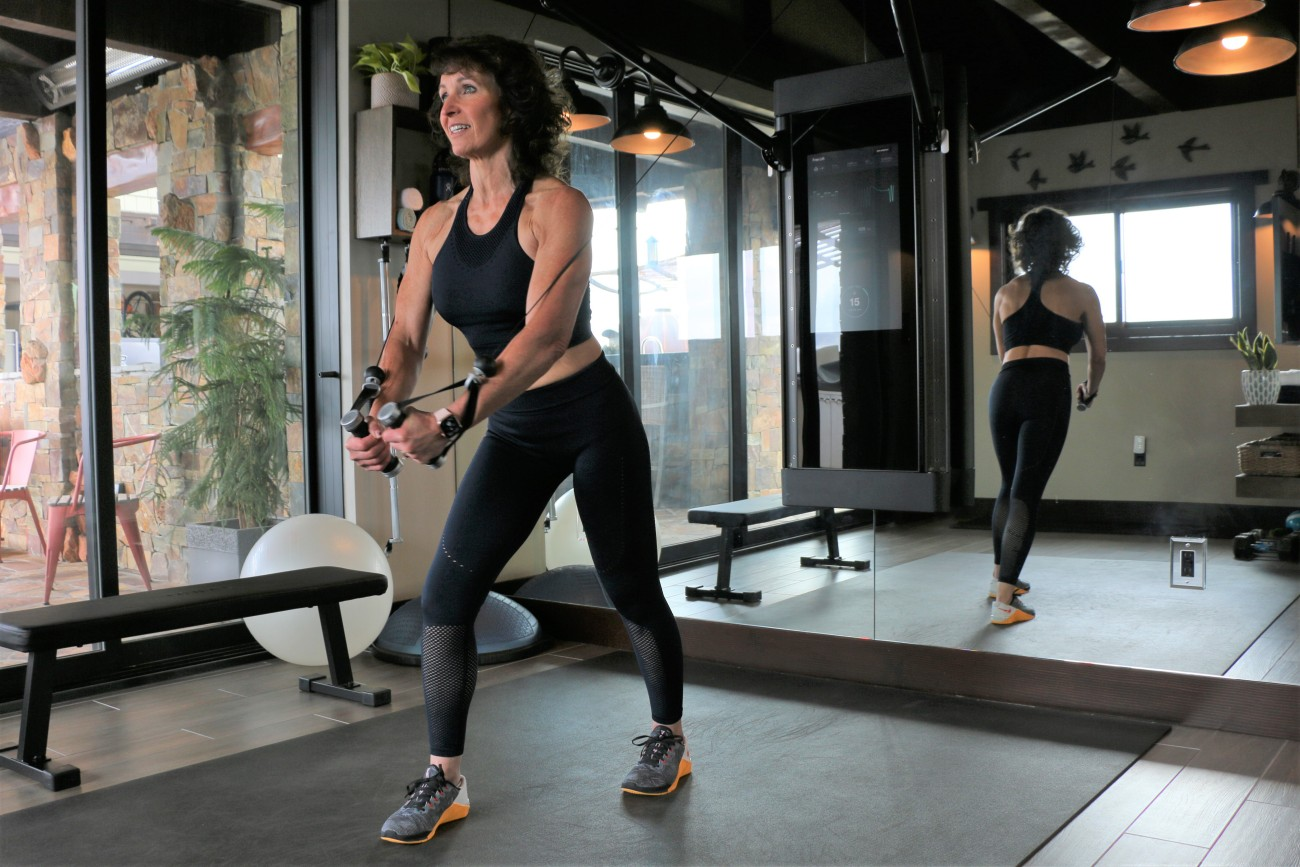 a woman works out on her Tonal machine in her gym where there are mirrors, she is smiling