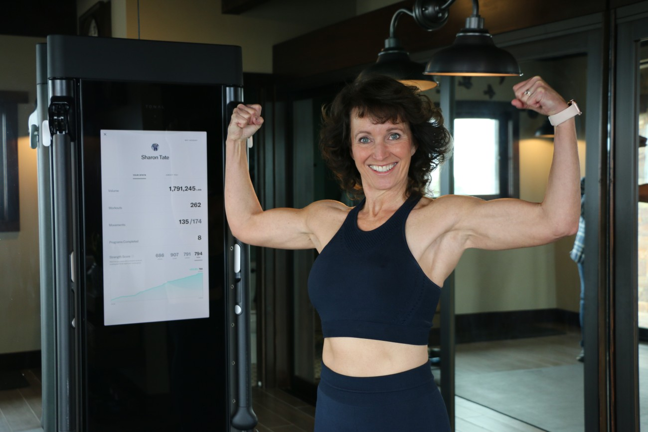 a woman smiling holds up her biceps proudly