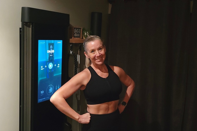 A woman in front of her Tonal exercise machine smiling