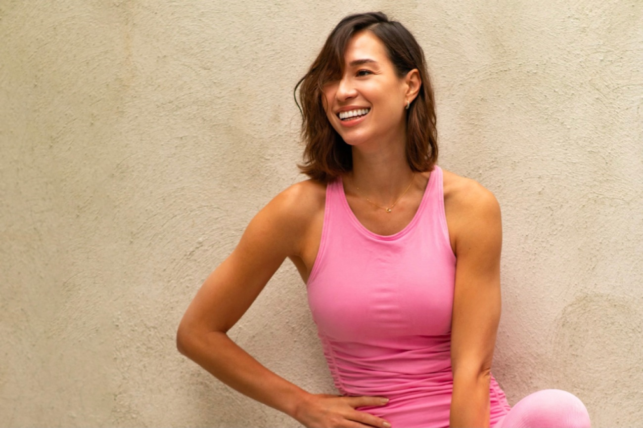 a woman smiling and leaning back against a wall