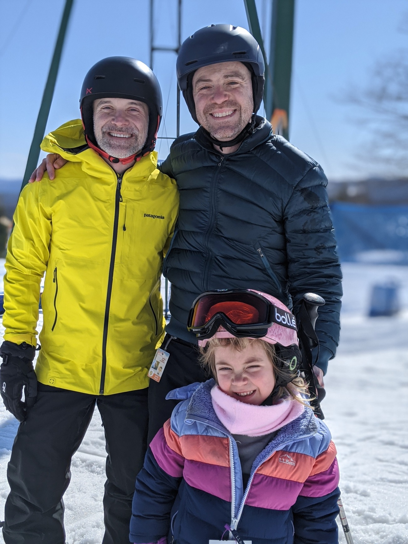 a man and his husband with their daughter in skiing gear in front a snowy mountain