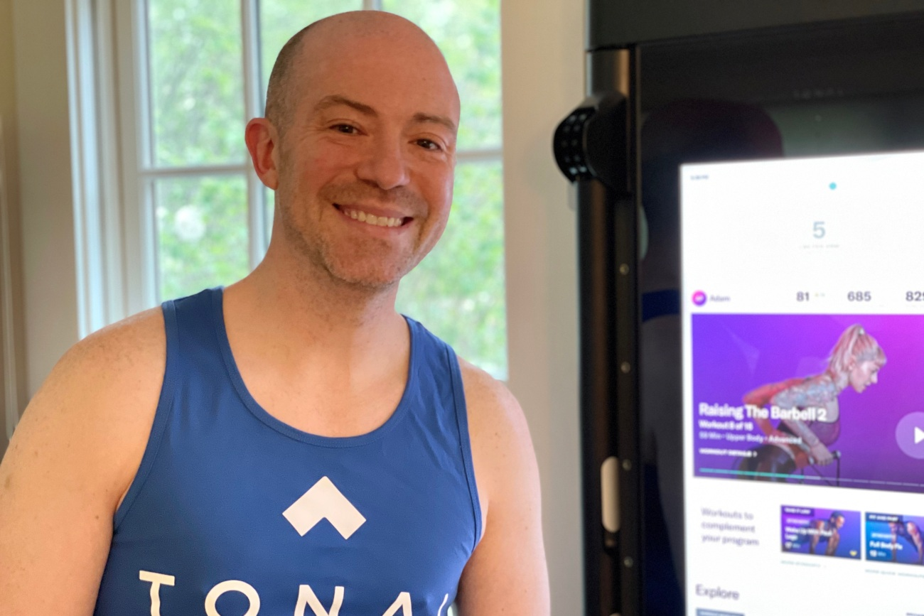 a man smiling in front of his tonal in a blue workout vest that say tonal