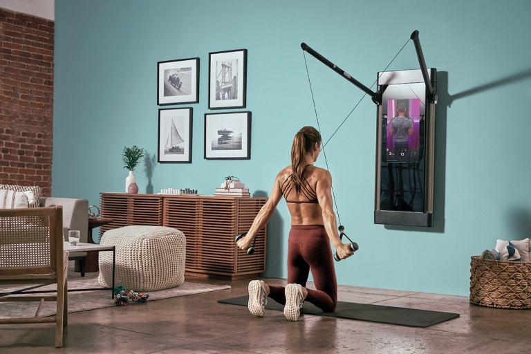 a woman kneels strong on her knees with her back to us as she performs a lat pull down with her muscles visible