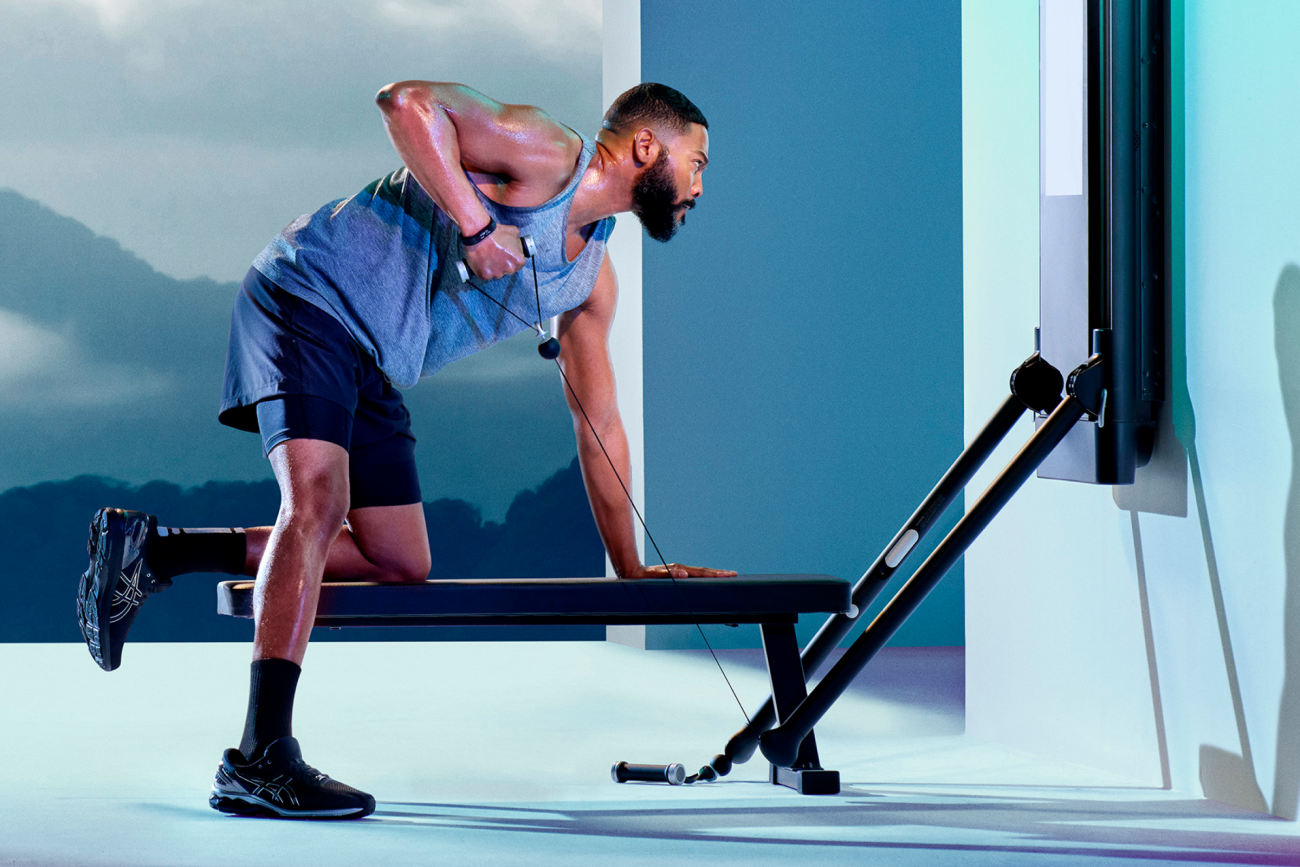 a man working on tonal doing an arm row with one knee on a bench