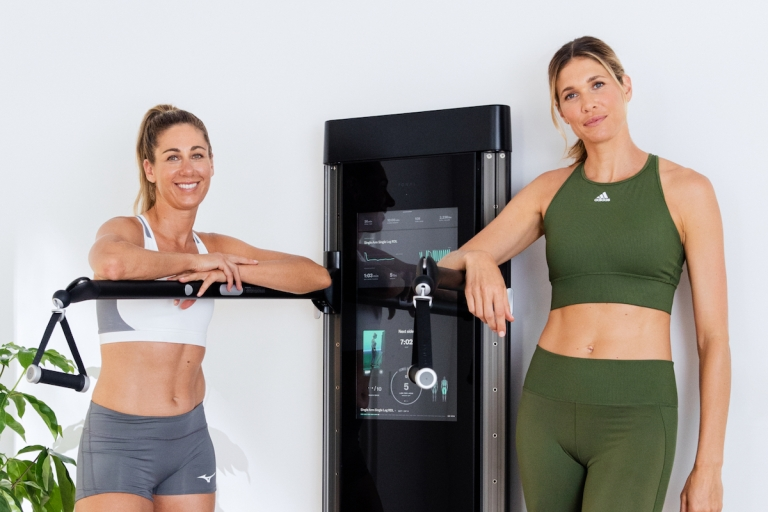 beach vollyball athletes april ross and alix klineman stand alongside their Tonal exercise machine smiling