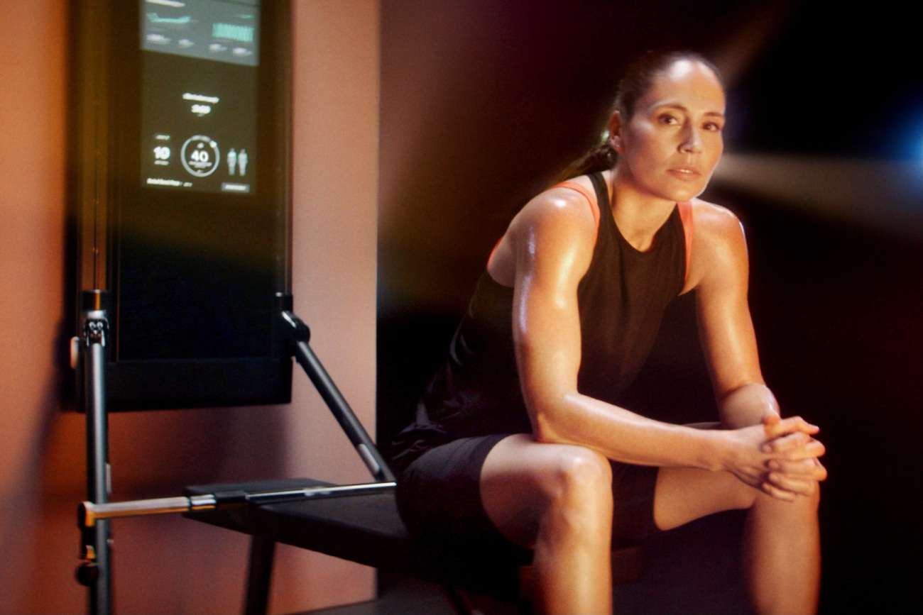 an athlete sits on a bench in front of the tonal exercise machine