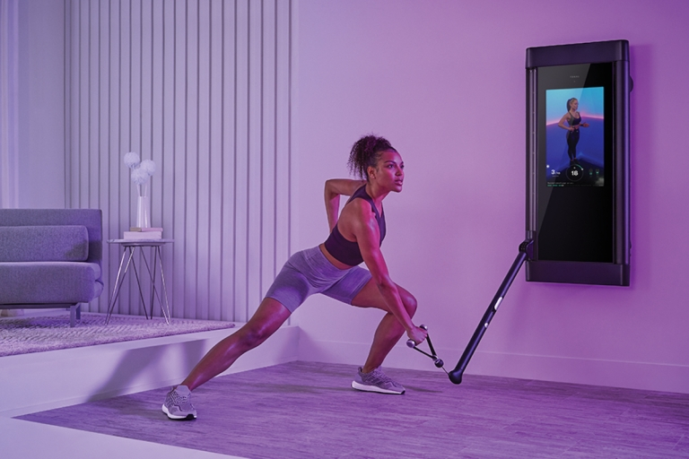 a woman using a tonal exercise machine to work out