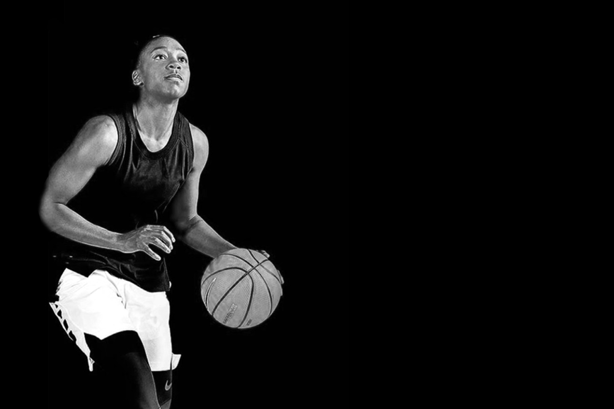 black and white image of a woman basketball player bouncing a ball