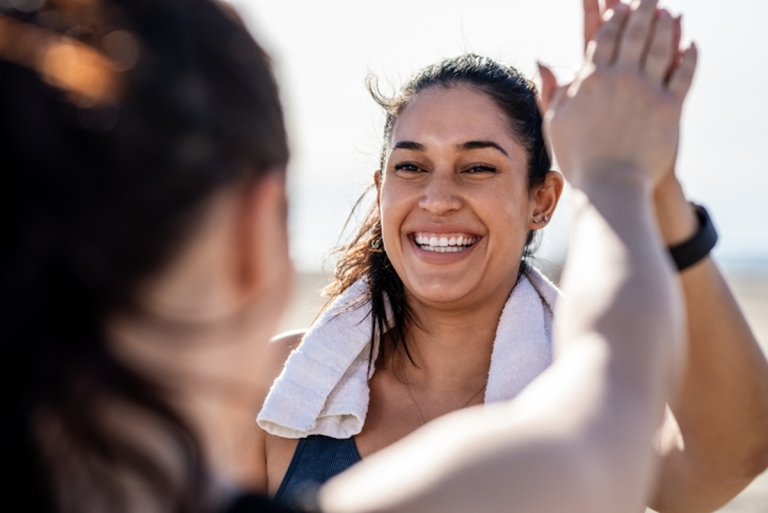 virtual fitness exercise with friends: Smiling woman giving high five to her friend after exercising. Woman looking happy after a successful workout session outdoors.