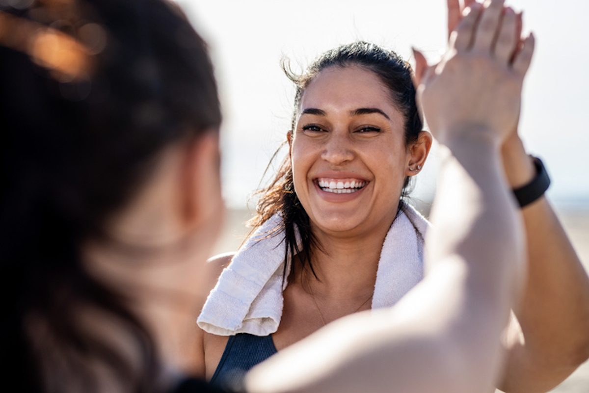 Smiling woman giving high five to her friend after exercising. Woman looking happy after a successful workout session outdoors.