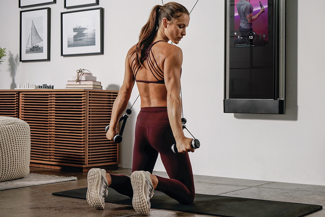 Woman working out at home on Tonal for muscular strength and hypertrophy.
