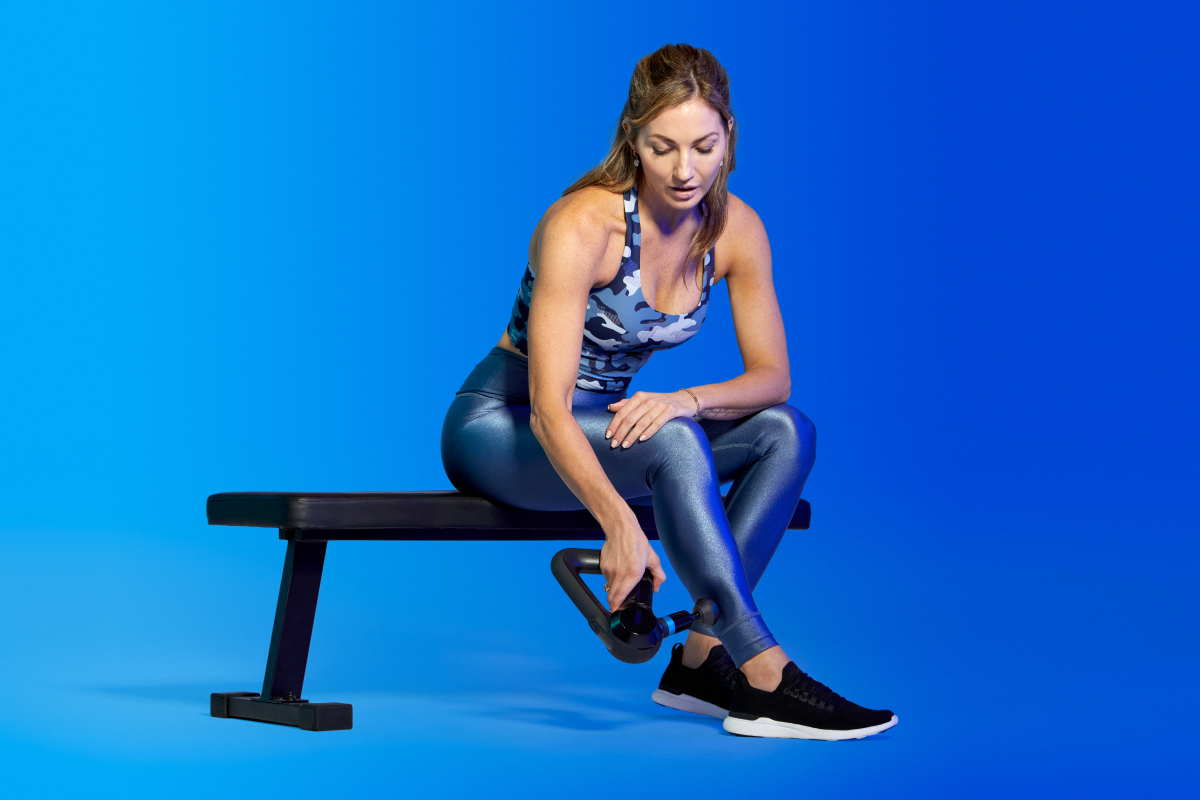 A woman using a Theragun for percussive therapy demonstrating a marathon recovery technique.