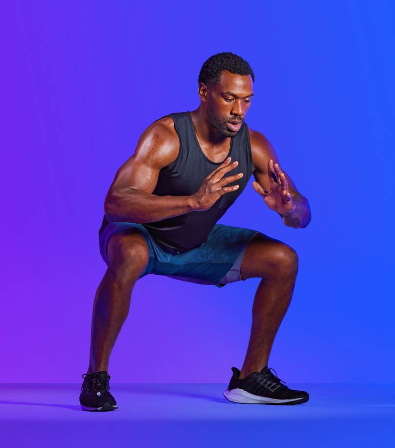 A man in workout clothes performs a squat.