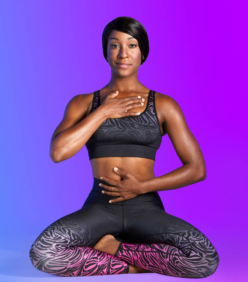 A woman in workout clothes performs a sitting yoga pose.