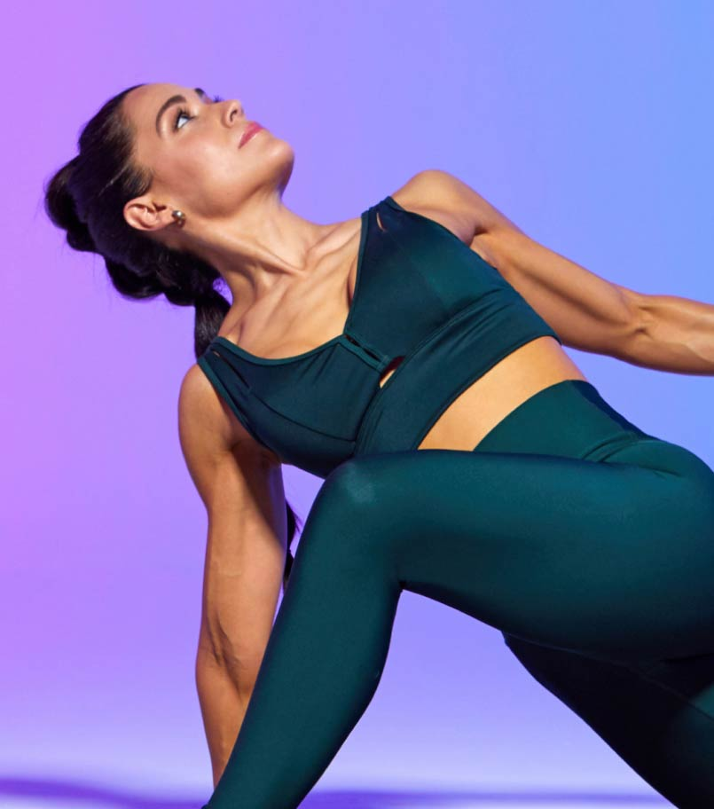 A woman in workout clothes performs a lunge stretch against a multi-colored backdrop.