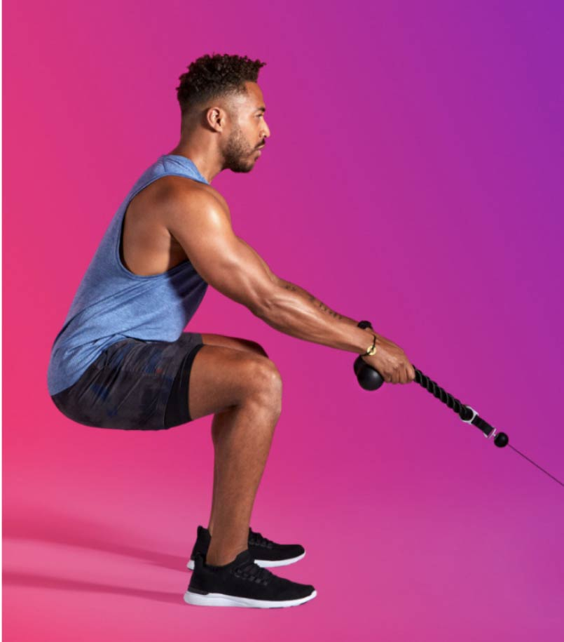 A man in workout clothes performs a squatting workout with a Tonal smart home gym machine on a multi-color backdrop.