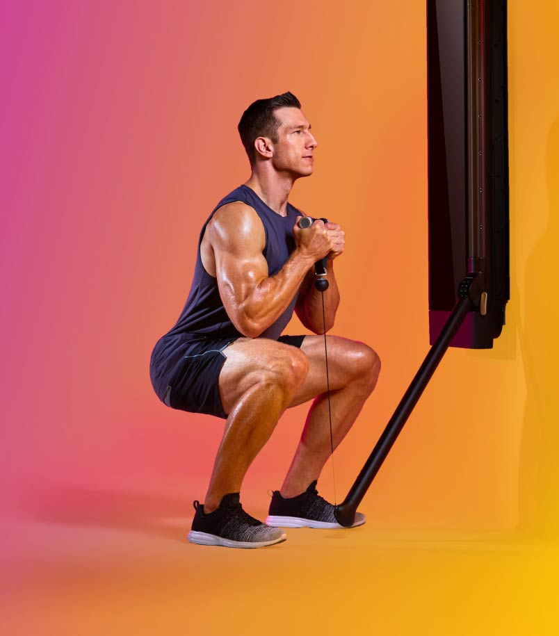 A man in workout clothes performs a lower body workout using a Tonal against a multi-colored backdrop.