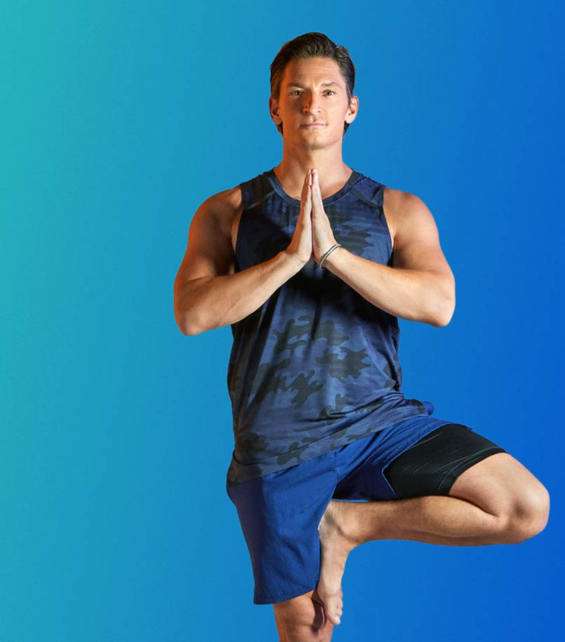 A man in workout clothes performs a yoga pose against a blue backdrop.